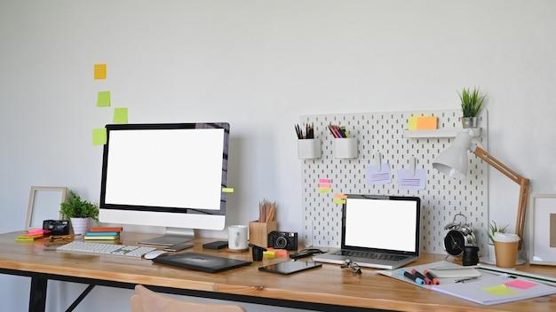 グラフィックデザイナーの作業台とそれに置くグラフィックデザイン機器の写真。白い空白の画面のノートパソコンとコンピューターのディスプレイは、広告の概念のためのスペースを残します。乱雑なワーキングデスクのコンセプト。
