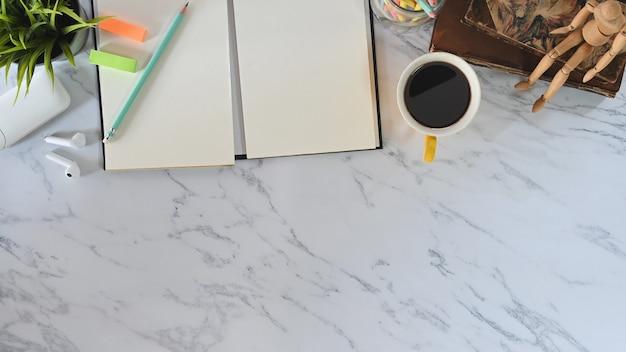 本、ノート、鉛筆、コーヒー、オフィスガジェット付きイヤホンを備えた大理石のトップビューオフィスデスク。