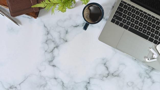 ラップトップ、コーヒー、イヤホン、ノートブック、大理石のテーブルの上に鉛筆を備えたモダンなオフィスデスク。