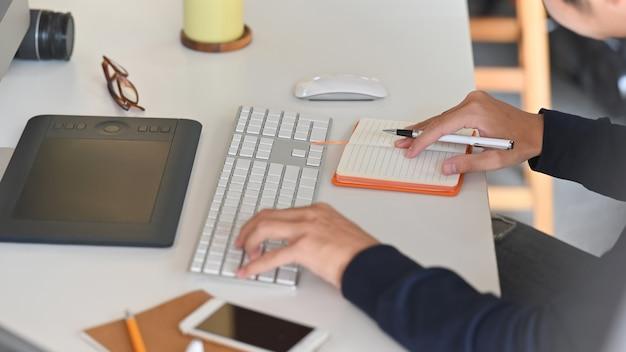 ワークデスクでの作業に集中しながら若い創造的な男のサイドショット。キーボード、マウス、ノート、ペン、スマートフォン、メガネ、カメラ、作業机の上。