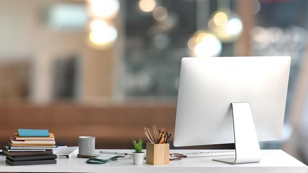 Рабочее место врача. позади монитора компьютера, держателя карандаша, кофейной чашки, стетоскопа, стопки книг, растение в горшке, на белом рабочем столе в экзаменационную комнату.