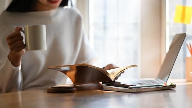 Обрезанное изображение красивой женщины, держащей кофейную чашку в руке, читающей книгу и сидящей перед своим компьютерным ноутбуком, надевающим деревянный стол над уютной гостиной
