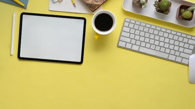 Изображение взгляд сверху красочного рабочего места. компас карандаша, кофейная чашка, тетрадь, маркеры, кактус, стилус и планшет с белым пустым экраном лежат на желтом столе.