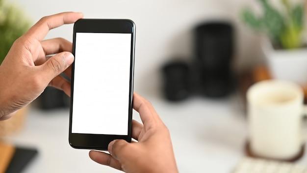 彼の白い作業机の上に白い空白の画面でトリミングされた黒いスマートフォンを持っているスマートな男の手の画像をトリミングしました。