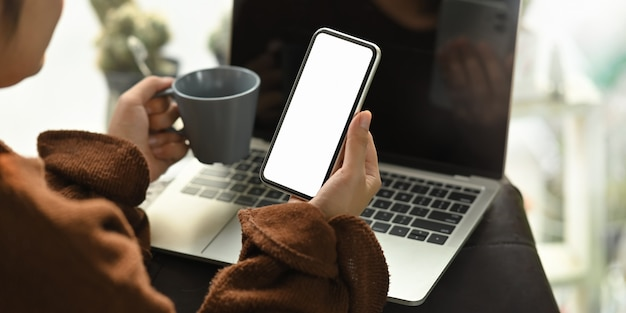 リビングルームの革のソファで彼女のラップトップの前に座っている間コーヒーカップと白い空白の画面のスマートフォンを保持しているクローズアップの女性。在宅勤務/リモートワーキングコンセプト。
