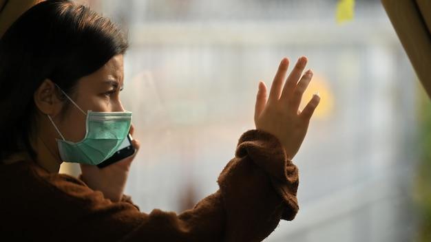モダンなリビングルームの窓に立っている間、スマートフォンを使用して医療用マスクを着ている若い女性の写真。自宅で検疫をしている女性。社会的距離の概念。