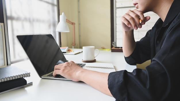 Руки человека взгляда со стороны используя портативный компьютер и думая идеи на домашнем офисе с подрезанной съемкой.