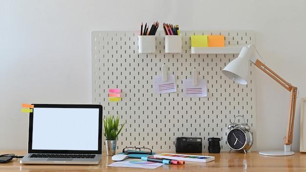 Творческое рабочее пространство портативного компьютера и стильный аксессуар на столе.
