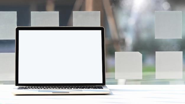 ガラス窓付きのモダンな作業テーブルに置く白い空白の画面を持つコンピューターのラップトップ。