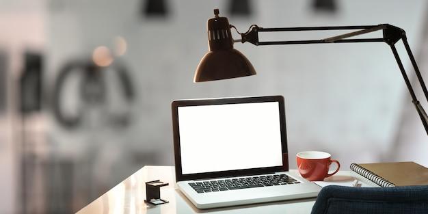作業机とコーヒーカップ、ランプ、メモ、ペンを置く白い空白の画面を持つコンピューターのラップトップ。