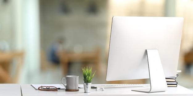整然としたワークスペースは、コンピューターモニターとオフィス機器に囲まれています。