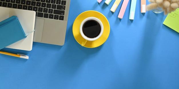 コーヒーカップの平面図の画像は、オフィス機器に囲まれたカラフルなテーブルの上に置いています。