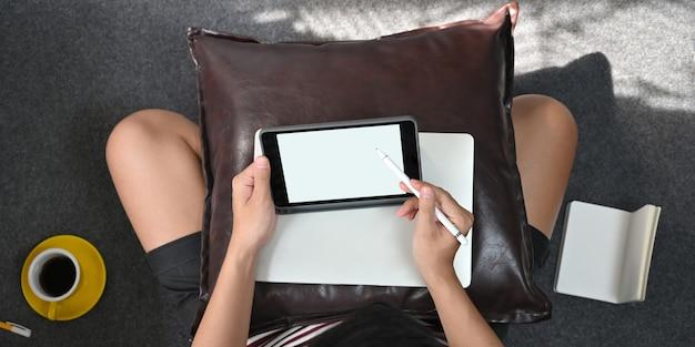 スマートな男のトップビューイメージは、スタイラスペンを使用して膝を置く白い空白の画面のコンピュータータブレットで描画しています。