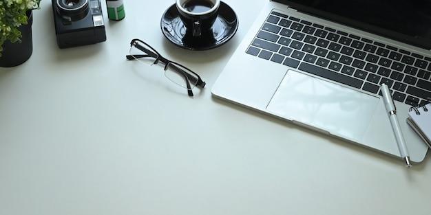 コンピューターのラップトップ、ペン、メガネ、コーヒーカップ、メモ、レトロなカメラ、フィルム、鉢植えに囲まれた白い作業机の画像を閉じます。