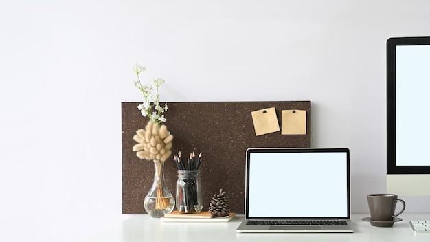 Белый пустой экран ноутбука ставит на белый рабочий стол, в окружении оргтехники.