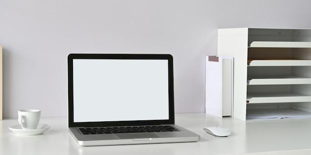 白い空白の画面のコンピューターラップトップは、オフィス機器に囲まれた白いワークスペースに置かれています。