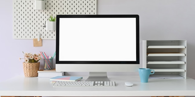 コンピューターのモニターは、オフィス機器に囲まれた白い作業机の上に置いています。