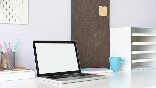 白い空白の画面コンピューターラップトップは、オフィス機器に囲まれた白い作業机の上に置いています。