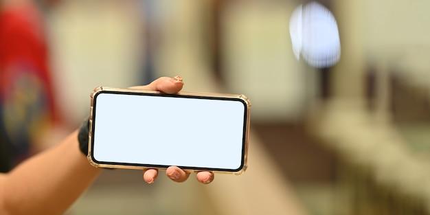 水平に白い空白の画面のスマートフォンを保持している女性のトリミングされた画像。携帯を持っている手
