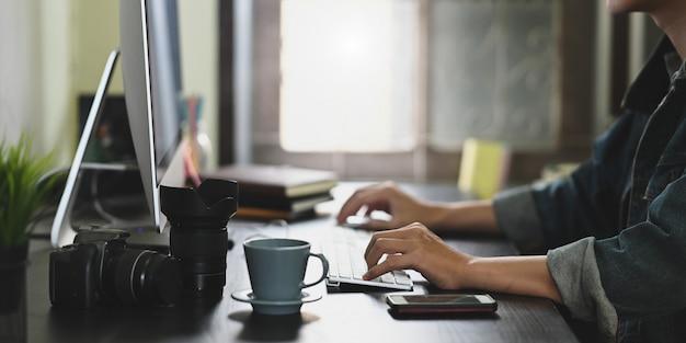 Руки фотографа набирают текст на беспроводной клавиатуре и используют мышь на рабочем столе.