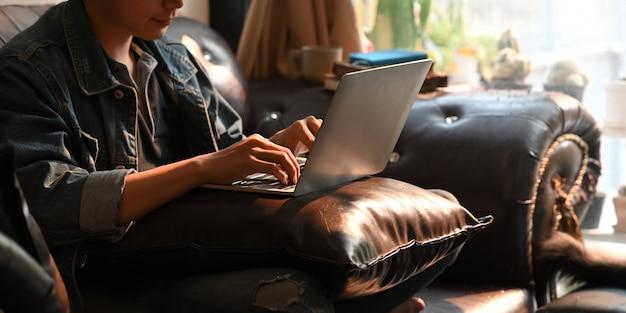 Человек печатает на компьютере ноутбук, который ставит его на колени, сидя на черном кожаном диване