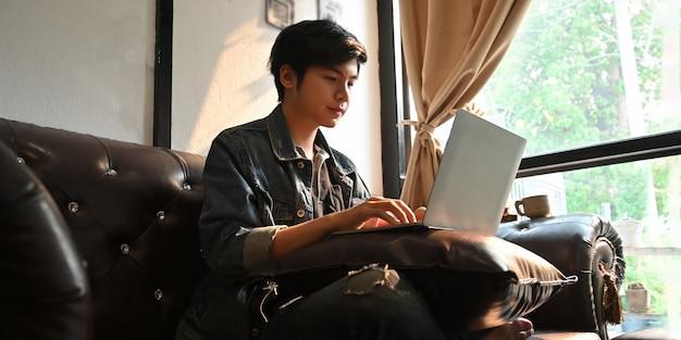 Человек печатает на компьютере ноутбук, который ставит его на колени, сидя на кожаном диване