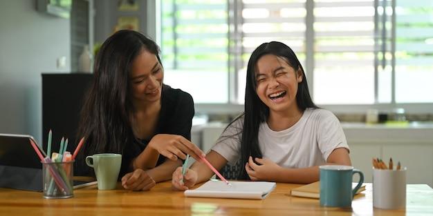 Мать сидит с дочерью и учит ее домашнее задание на деревянный рабочий стол.
