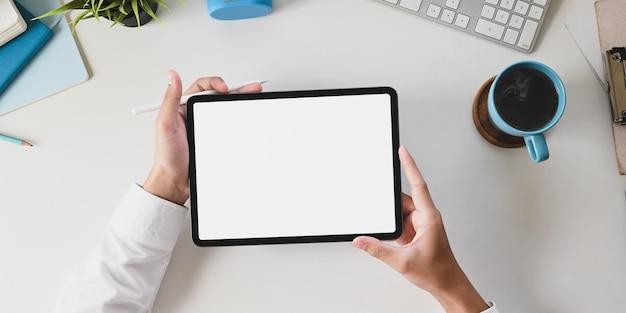 Руки стола офиса держат белую таблетку компьютера пустого экрана на белом работая столе.