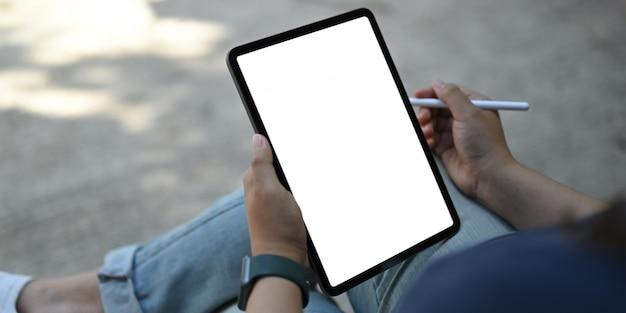 Женщина держа белую таблетку пустого экрана и ручку грифеля на месте для работы.