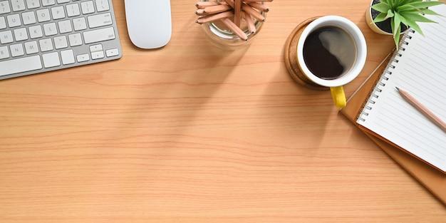 Деревянное рабочее место окружено кофейной чашкой и личным оборудованием.