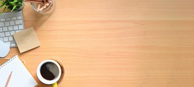 Простой вид сверху деревянный стол - креативная плоская планировка офисного стола. компьтер-книжка, тетради и кофейная чашка на деревянной предпосылке.
