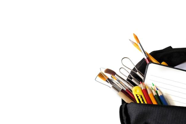 スクールバッグと教育機器の白い画面で、学校のコンセプトに戻る