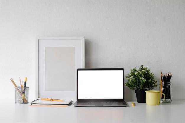 コーヒー、プラット、フォトフレームのコピースペースオフィスのマグカップで作業スペースにノートパソコンをモックアップ。
