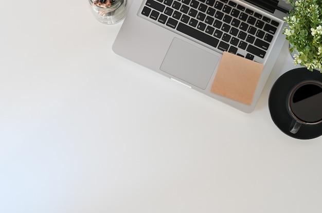 ラップトップコンピューター、コーヒー、トップビューコピースペースに付箋のオフィスデスク。