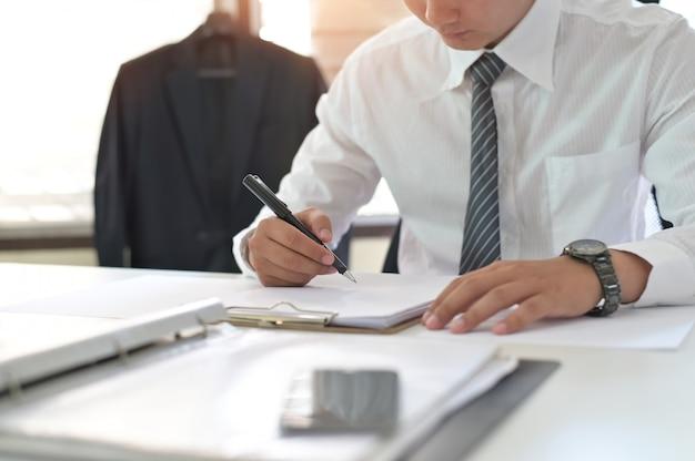 仕事場で契約を結ぶ契約に署名する実業家のショットをトリミングしました。