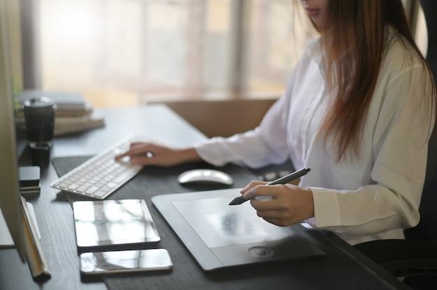 グラフィックデザイナーの仕事、デジタルペンを使用して女性をタブレットでスケッチし、創造的な机の上のコンピューターでの作業。
