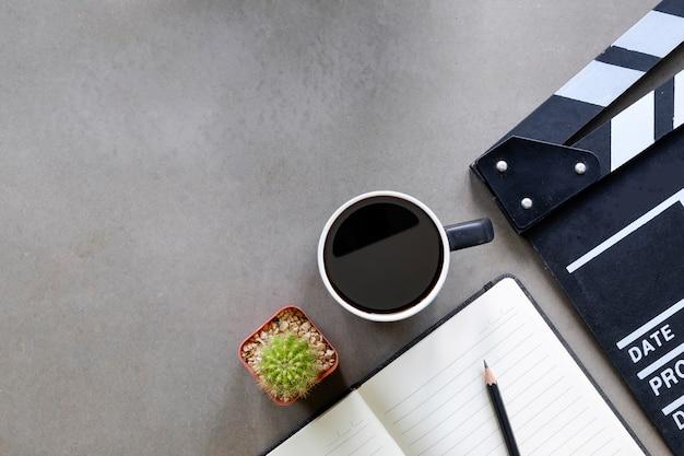 メモ帳の紙、一杯のコーヒー、監督テーブルトップビューとコピースペースにサボテンの映画クラッパー。