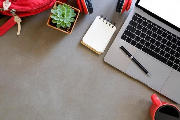 学校のラップトップコンピューター、バッグ、ノートブック紙、コーヒーのカップとトップビューテーブルの上にヘッドフォンに戻る。