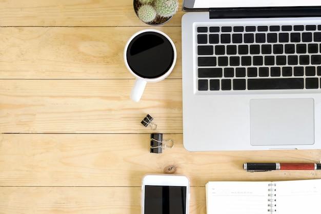ラップトップコンピューター、コーヒー、ペン、サボテンと木製の机の上のスマートフォンのトップビューワークスペース。