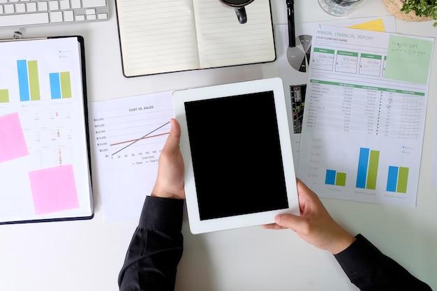ファイナンスペーパーレポートとトップビューのオフィスの机の上のモックアップタブレットを使用しての実業家。