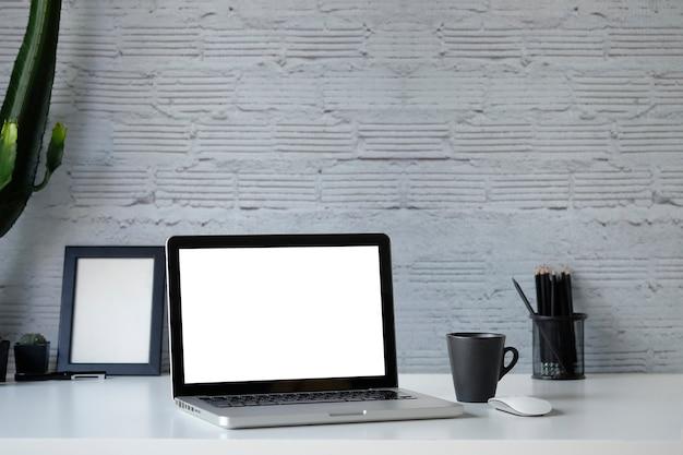 Ноутбук макета рабочей области, кофе и кактус на столе в офисе и канцелярских товарах с фоном кирпичной стены.