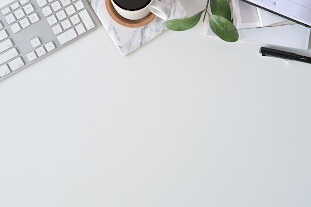 Плоский лежал вид сверху офисный стол. рабочая область с клавиатурой и канцелярскими принадлежностями.