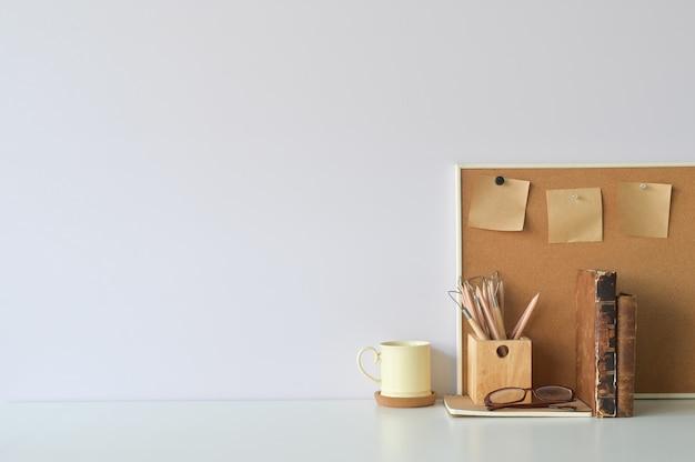 オフィスのワークスペースのコーヒー、鉛筆、書籍、コピースペースを持つボード上の付箋。