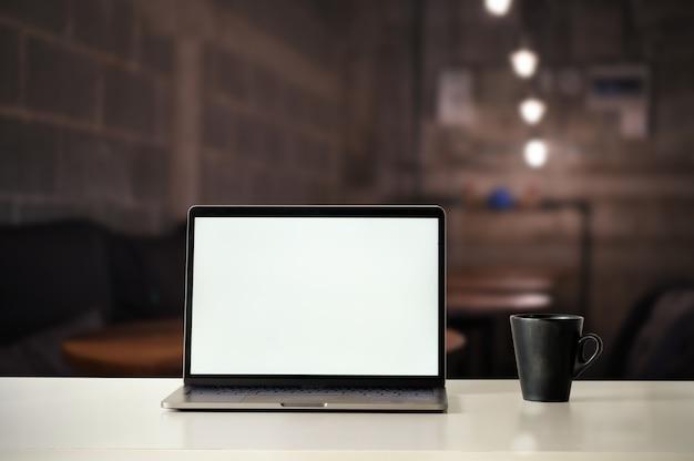 モックアップラップトップコンピューターと夜のカフェでコーヒー。