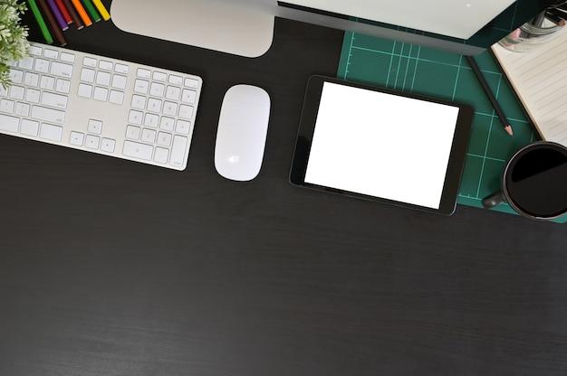 モックアップタブレットコンピューターと黒いテーブル、上面の事務機器のクリエイティブデスクワークスペース。