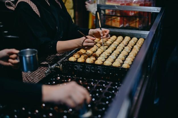たこ焼きを作るクローズアップ手。たこ焼きは、玉日本のおやつ人気のおやつです。