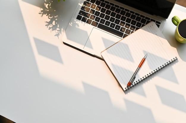 トップビューオフィスデスクラップトップとテーブルの上にペンでノート。