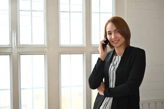 Секретарь разговаривает по телефону с нетерпением и улыбкой.