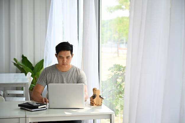 アジア人の男性がカフェでラップトップコンピューターを使用しています。
