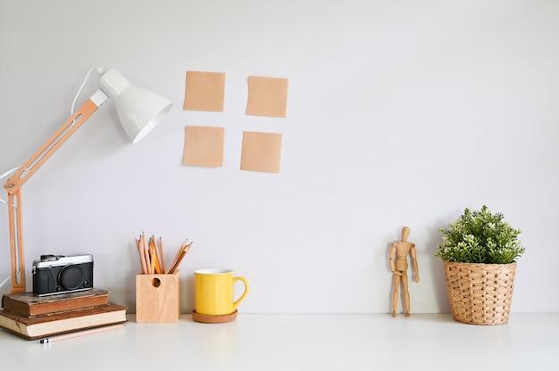 Рабочая область таблицы камеры, кружка кофе, карандаш и книги на творческий стол.